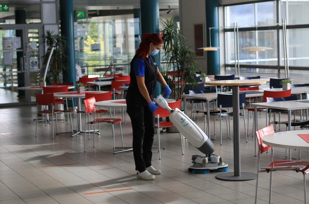 Vastuullisuus näkyy käytetyissä laitteissa: kuvassa puhtauspalveluiden työntekijä puhdistaa ruokailusalia uudenaikaisella kahdella kädellä ohjattavalla laitteella, joka tekee työn mekaanisesti ilman suuria vesimääriä.